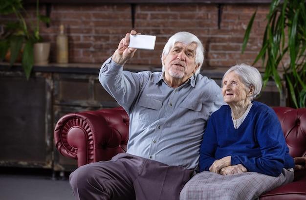Senior paar selfie met slimme telefoon zittend op de bank thuis