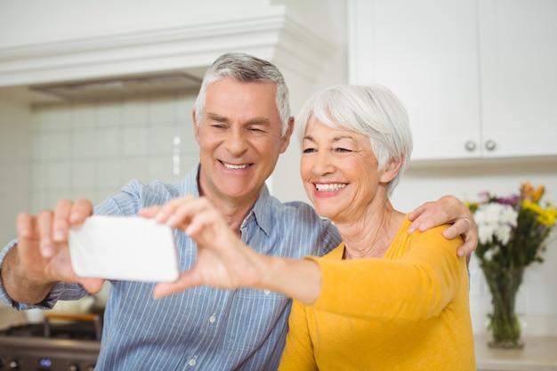 Senior paar selfie te nemen van mobiele telefoon in de keuken