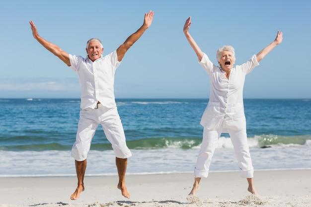 Senior paar springen op het strand