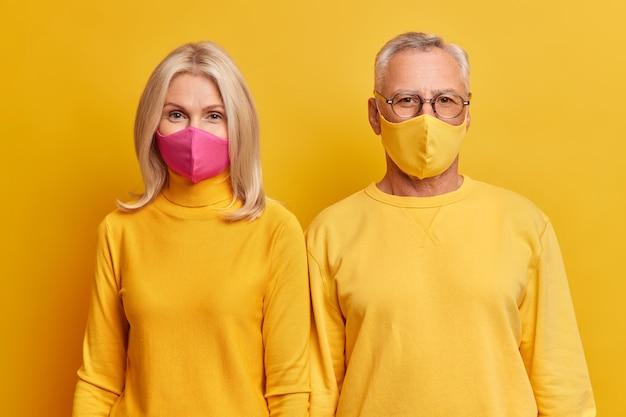 Senior paar staan dicht bij elkaar thuis blijven tijdens quarantaine dragen beschermende gezichtsmaskers dragen gele kleding serieus naar voren kijken