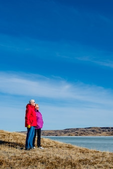 Senior paar staande met uitzicht op een met ijs bedekte lake diefenbaker