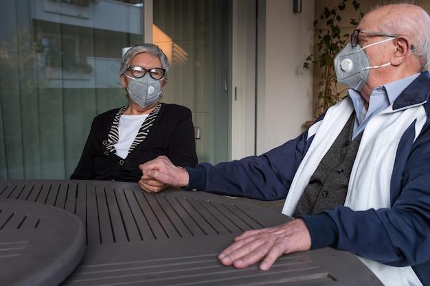 Senior paar thuis met maskers