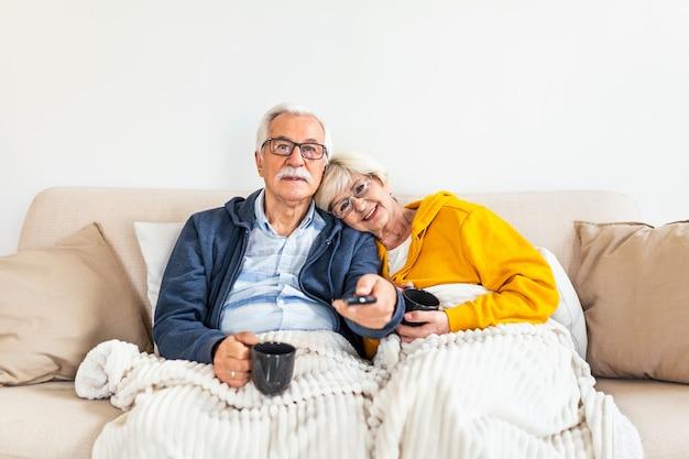Senior paar thuis ontspannen op de bank, tv kijken, man schakelen tussen kanalen met afstandsbediening, koffie drinken