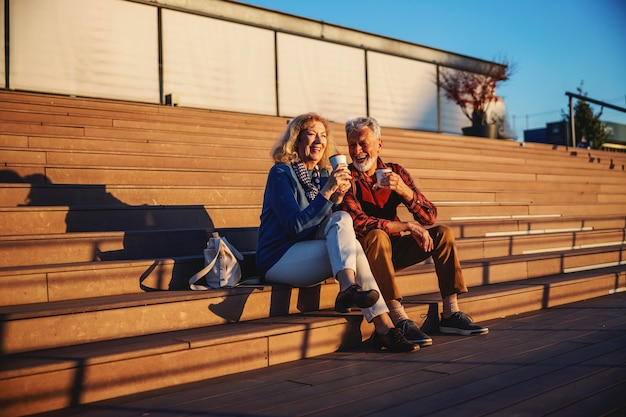 Senior paar verliefd buiten zitten op de trap en koffie drinken om te gaan.