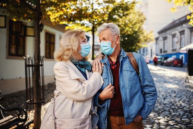 Senior paar verliefd op beschermende maskers op buitenshuis staan en kijken naar elkaar.