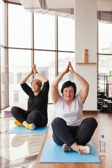 Senior paar yoga doen