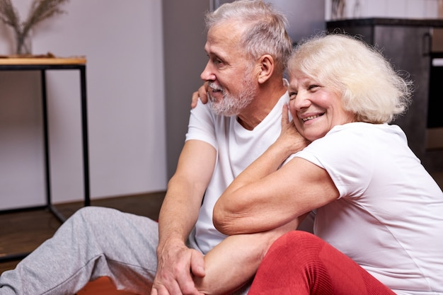 Senior paar zitten samen op de grond te rusten na sportoefeningen, genieten van gezond en sportief zijn, glimlachen knuffelen