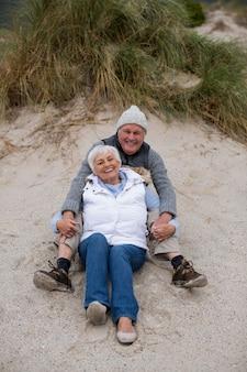 Senior paar zitten samen op strand