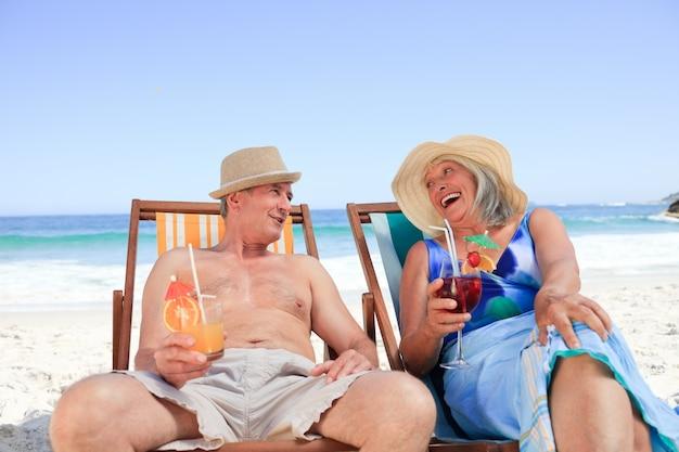 Senior paar zittend op de ligstoelen