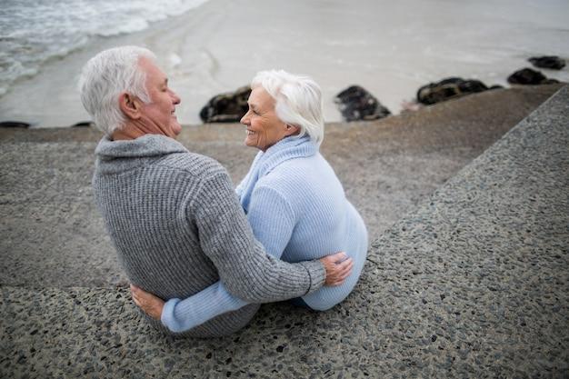 Senior paar zittend op rots op het strand