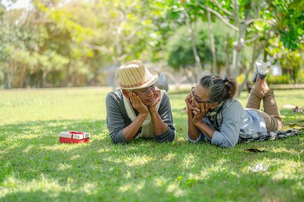 Senior, paren, pensioen, verzekeringen, ouderen, lifestyle concept. senior koppels praten 's ochtends op het buitengazon over levensverzekeringsplannen met een gelukkig pensioenconcept.