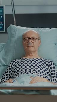 Senior patiënt die in ziekenhuisbed ligt op de zorgafdeling