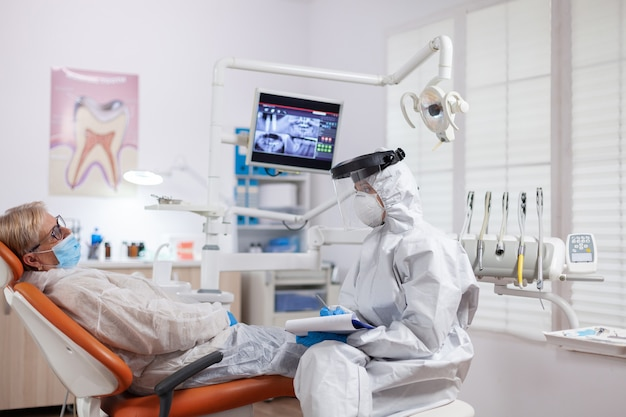 Senior patiënt die tandpijn presenteert met een hazmat-pak tegen coronavirus bij de tandarts. oudere vrouw in beschermend uniform tijdens medisch onderzoek in tandheelkundige kliniek.