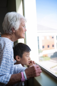 Senior patiënt en jongen kijkt uit het raam