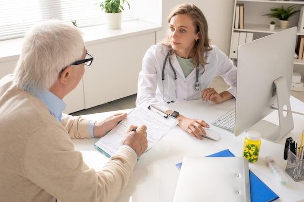 Senior patiënt medisch document invullen zittend door bureau voor jonge arts raadplegen hem over wat te schrijven in papier