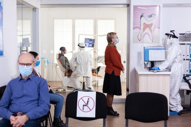Senior patiënt met gezichtsmasker in gesprek met tandartsassistent gekleed pbm-pak met sociale afstand in wachtruimte