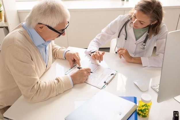 Senior patiënt met pen wijzend op medisch document in klembord terwijl hij zijn arts een vraag stelt over een van de punten in klinieken