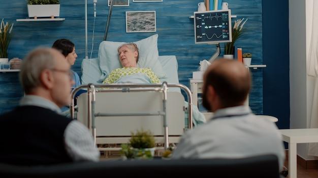 Senior patiënt met ziekte in gesprek met verpleegster over behandeling