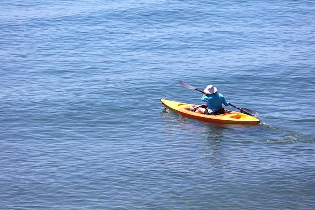 Senior persoon met kajakzeilen op de blauwe zee