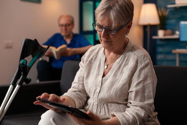 Senior persoon met krukken kijken naar moderne tablet