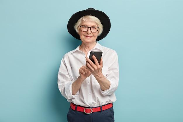 Senior positieve gerimpelde vrouw blij met nieuwe handige functies van moderne gadget