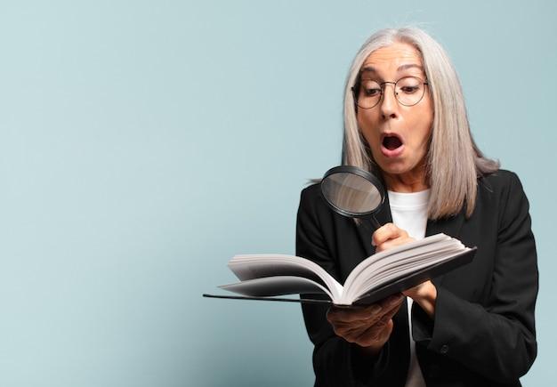Senior pre vrouw met een boek en een vergrootglas. zoekconcept