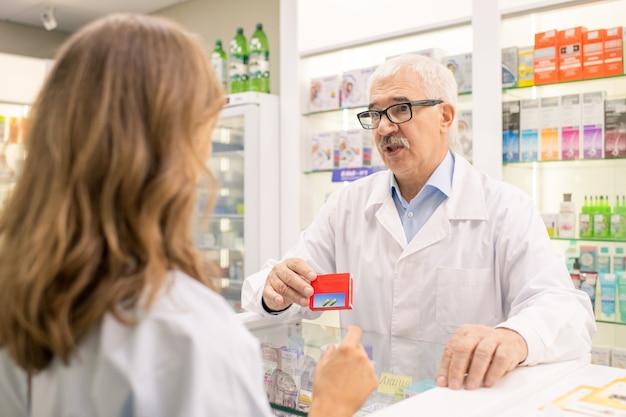 Senior professionele apotheker pakket van nieuwe effectieve geneeskunde tonen terwijl het aanbevelen aan jonge vrouwelijke cliënt in drogisterij