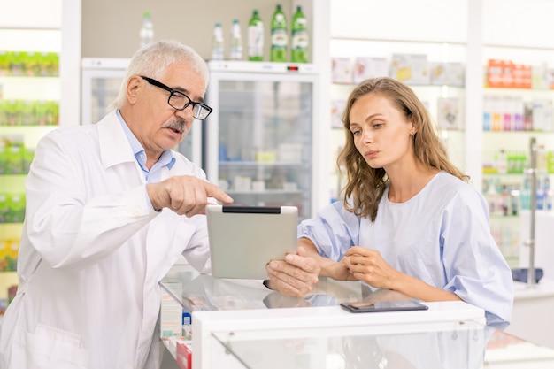 Senior professionele werker van hedendaagse drogisterij die zijn jonge vrouwelijke stagiair online informatie toont over nieuwe anti-covid19-geneeskunde