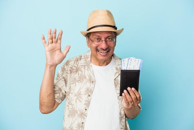 Senior reiziger indiase man van middelbare leeftijd met paspoort geïsoleerd op blauwe achtergrond die een aangename verrassing ontvangt, opgewonden en handen opsteekt.
