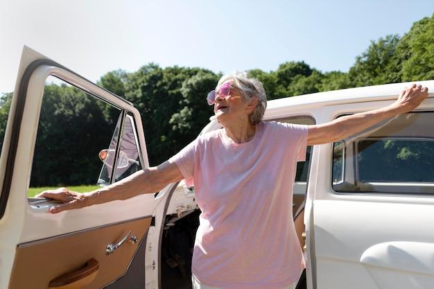 Senior reiziger met rode zonnebril naast haar auto