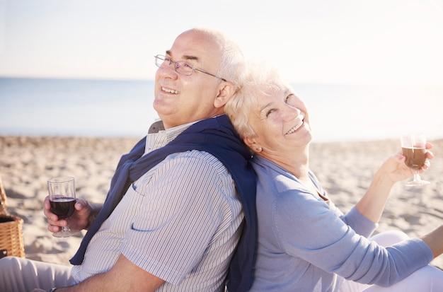 Senior rug aan rug zitten en wijn drinken. senior paar in het strand, pensioen en zomervakantie concept