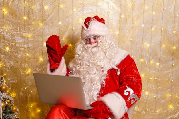 Senior santa in rode klederdracht online chatten op laptop tijdens videogesprek over kerstmis
