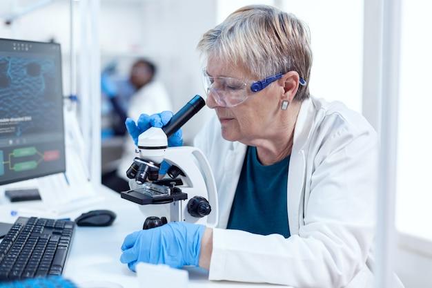 Senior scheikundige wetenschapper die genetisch onderzoek doet met behulp van een microscoop. oudere onderzoeker die wetenschappelijk onderzoek uitvoert in een steriel laboratorium met behulp van een moderne technologie.