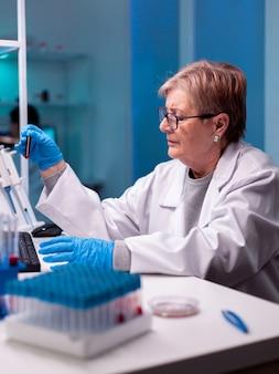Senior scheikundige wetenschapper experiment met bloed in reageerbuis