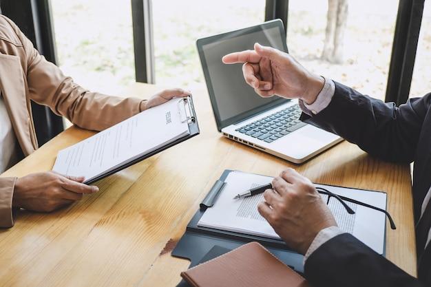 Senior selectiecommissie manager stelt vragen aan sollicitant over werkgeschiedenis, colloquydroom