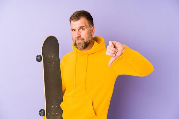 Senior skater man geïsoleerd op paarse achtergrond met een afkeer gebaar, duimen naar beneden. meningsverschil concept.