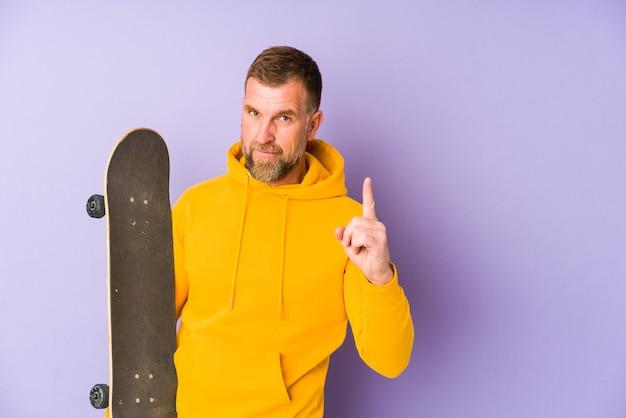 Senior skater man geïsoleerd op paarse achtergrond met nummer één met vinger.