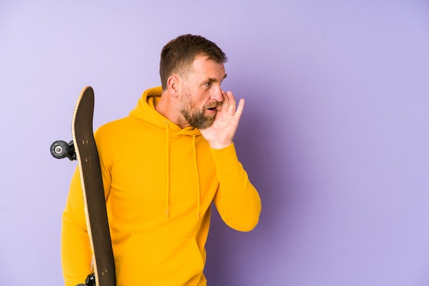 Senior skater man geïsoleerd op paarse muur zegt een geheim heet remmend nieuws en kijkt opzij