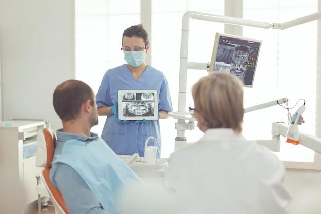 Senior somatologievrouw praat met zieke man over tandgezondheidszorg