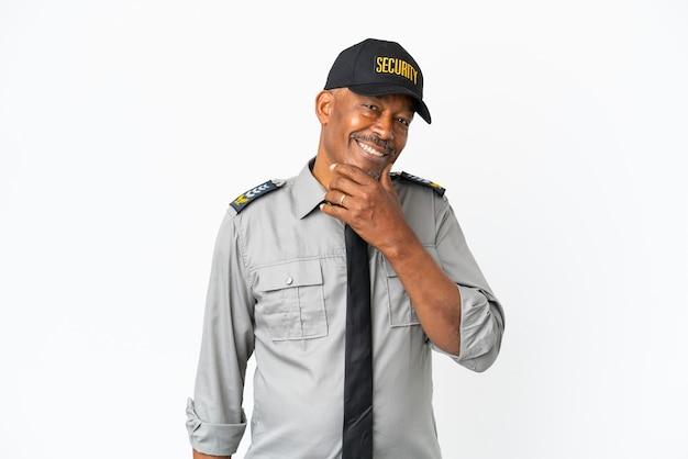 Senior staf man geïsoleerd op een witte achtergrond op zoek naar de kant en glimlachend