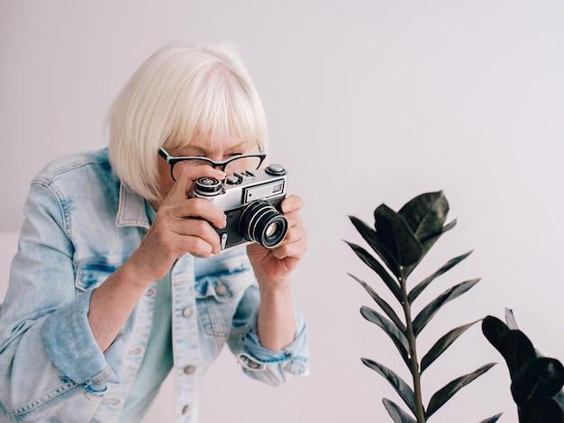 Senior stijlvolle vrouw met grijs haar in een bril met spijkerjasje die foto's maakt van bloemen met een filmcamera