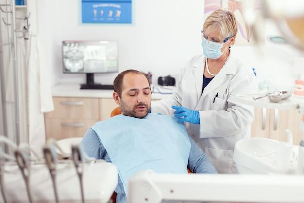 Senior stomatoloog helpt patiënt om op te staan na een tandheelkundige ingreep tijdens het kantoor van de medische stomatologiekliniek