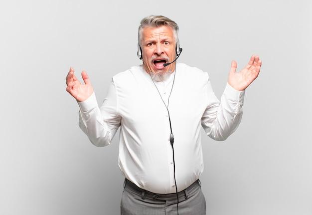 Senior telemarketeer blij, opgewonden, verrast of geschokt, glimlachend en verbaasd over iets ongelooflijks