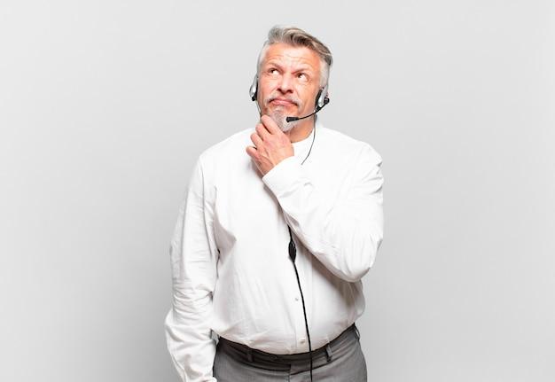 Senior telemarketeer denkt, voelt zich twijfelachtig en verward, met verschillende opties, zich afvragend welke beslissing hij moet nemen