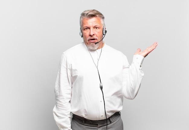 Senior telemarketeer die verrast en geschokt kijkt, met open mond terwijl hij een object vasthoudt met een open hand aan de zijkant