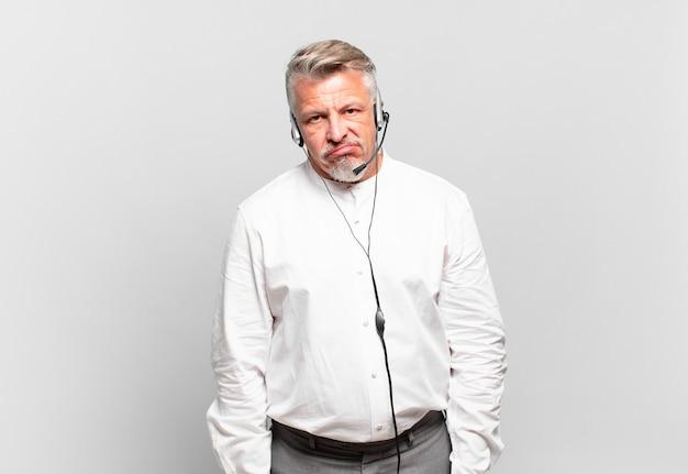 Senior telemarketeer die zich verward en verward voelt, met een stomme, verbijsterde uitdrukking die naar iets onverwachts kijkt