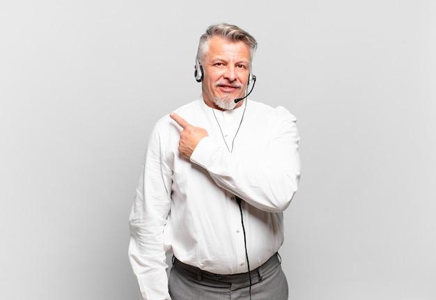 Senior telemarketeer lacht vrolijk, voelt zich gelukkig en wijst naar de zijkant en naar boven en toont een object in de kopieerruimte