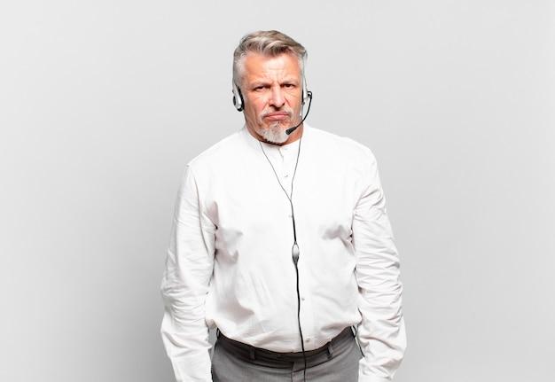 Senior telemarketeer voelt zich verdrietig, overstuur of boos en kijkt opzij met een negatieve houding, fronsend in onenigheid