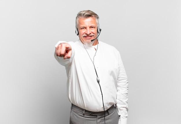 Senior telemarketeer wijzend op camera met een tevreden, zelfverzekerde, vriendelijke glimlach, jou kiezen