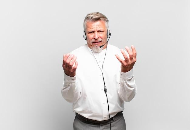 Senior telemarketeer ziet er wanhopig en gefrustreerd, gestrest, ongelukkig en geïrriteerd uit, schreeuwend en schreeuwend